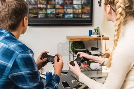 Photo for Back view of teens playing video game at home - Royalty Free Image