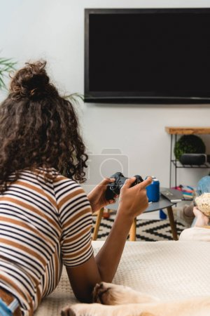 african american girl playing video game at home