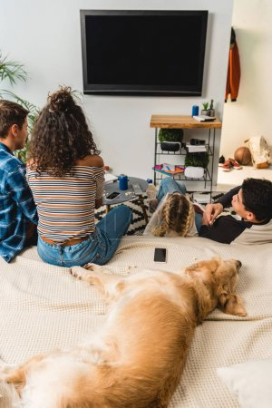 four teens watching tv and dog lying on bed