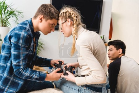 Photo for Boy and girl aggressively touching with foreheads while playing video game - Royalty Free Image