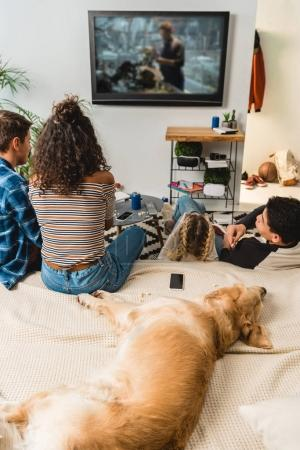 teens playing video game and dog lying on bed