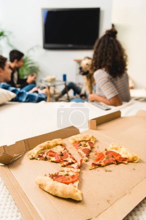 group of friends watching tv with pizza on foreground