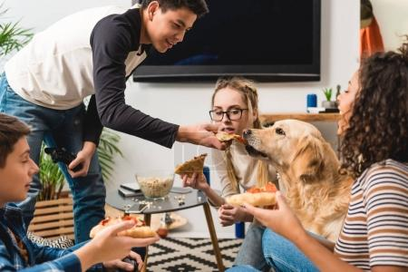 teenager giving piece of pizza to dog