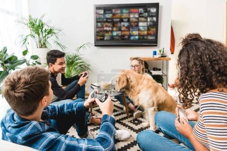 Photo for Group of four multiethnic teens playing video game at home - Royalty Free Image