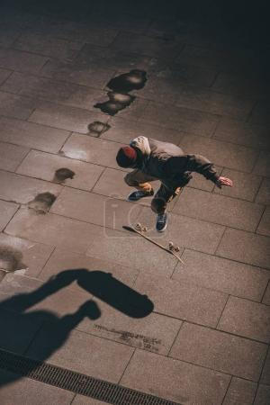 high angle view of skateboarder performing jump trick outdoors at late night