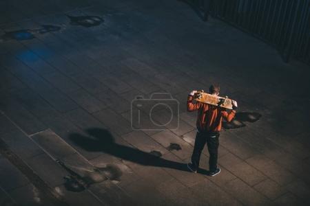 Photo pour Vue grand angle du skateboarder debout avec planche sur les épaules - image libre de droit
