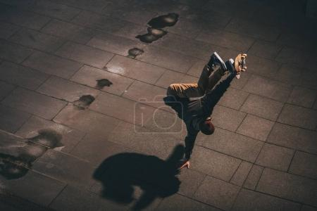 high angle view of professional skateboarder performing trick and standing on one hand