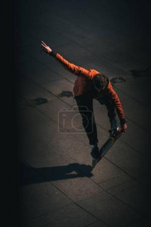 high angle view of skateboarder balancing on board at late night