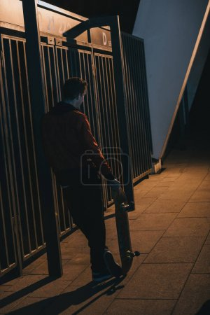 Photo for Man standing with skateboard outdoors at late night - Royalty Free Image