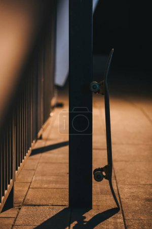 Photo for Skateboard leaning on pole at late night - Royalty Free Image