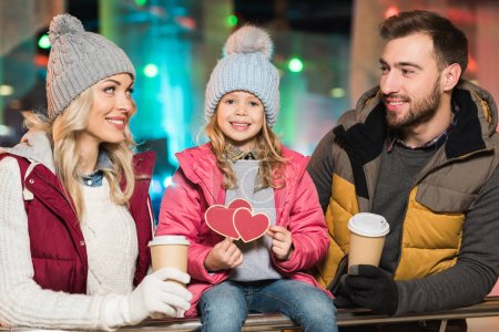 Photo for Happy parents with coffee to go looking at cute little daughter holding hearts symbol on rink - Royalty Free Image
