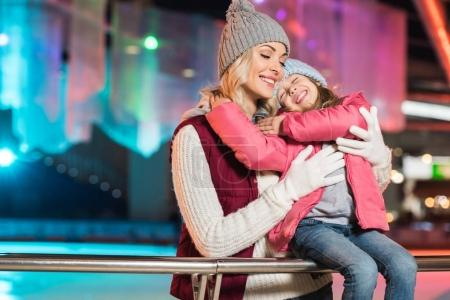 beautiful happy mother and daughter with closed eyes hugging on rink