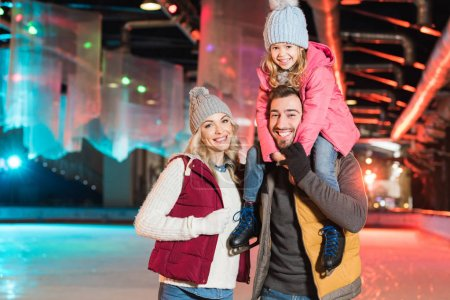 Photo for Happy young family smiling at camera while spending time together on rink - Royalty Free Image
