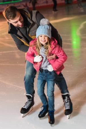 beautiful happy father and daughter hugging and having fun while skating on rink