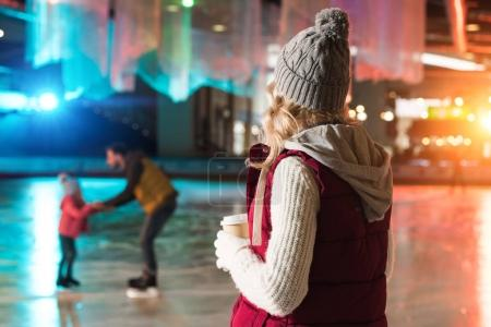 young woman drinking coffee from paper cup and looking at happy family skating behind on rink