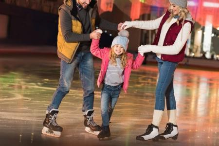 cropped shot of happy parents teaching adorable little daughter skating on rink
