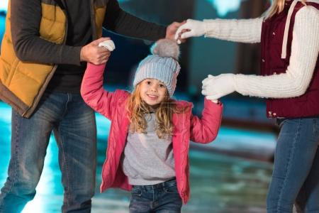 cropped shot of happy young family with adorable daughter standing together on rink