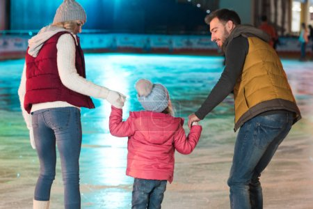 Photo for Back view of young family with one kid holding hands and skating on rink - Royalty Free Image