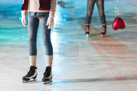 Photo for Cropped shot of young woman standing on rink while boyfriend with heart shaped balloon standing behind - Royalty Free Image