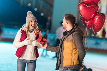 Photo pour Jeune homme tenant coeur en forme de ballons et la présentation coffret à copine excitée sur patinoire - image libre de droit