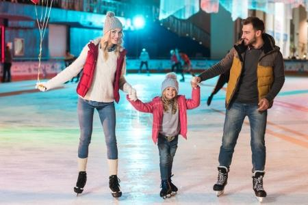 happy young family holding hands and smiling at camera on skating rink