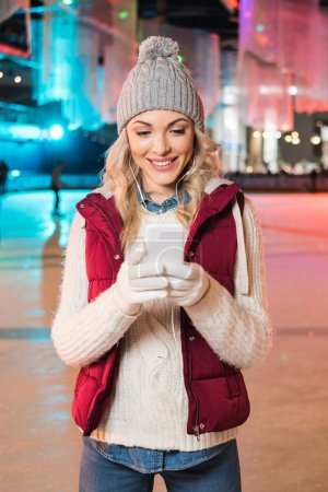 attractive smiling young woman in earphones using smartphone on rink