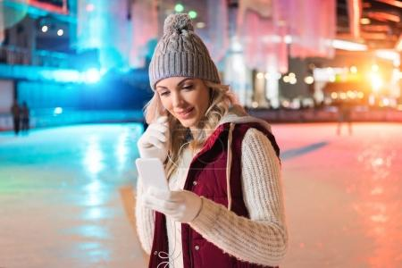 smiling young woman holding smartphone and listening music in earphones on rink