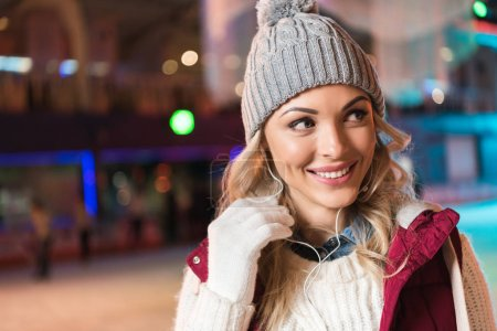 cheerful young woman in earphones looking away while ice skating on rink