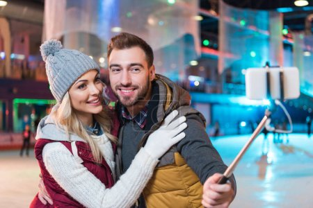 beautiful smiling young couple taking selfie with smartphone on rink