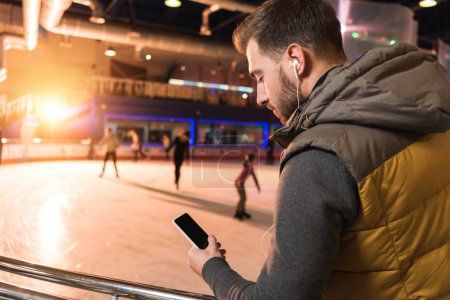 handsome young man in earphones using smartphone with blank screen on rink
