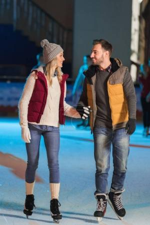 happy young couple in love holding hands and smiling each other while skating on rink