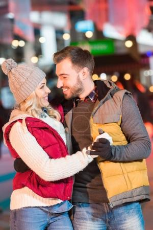 beautiful young couple in love holding hands and smiling each other on rink