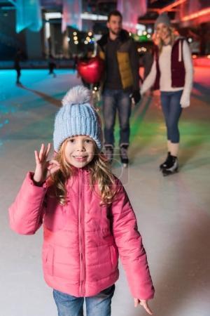 Photo pour Mignonne petite fille montrant ok signe et sourire à la caméra tout en patinant sur glace avec les parents sur la patinoire - image libre de droit