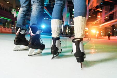 low section of couple in skates ice skating on rink