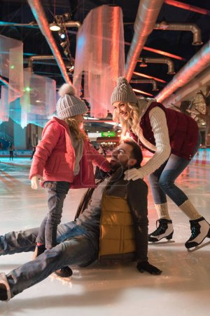 Photo pour Jeune femme avec jolie fille regardant rire homme tombant sur la patinoire - image libre de droit