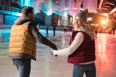 back view of happy young couple holding hands and skating on rink