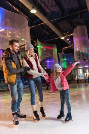 Foto de Familia joven feliz con un niño a patinar en pista - Imagen libre de derechos