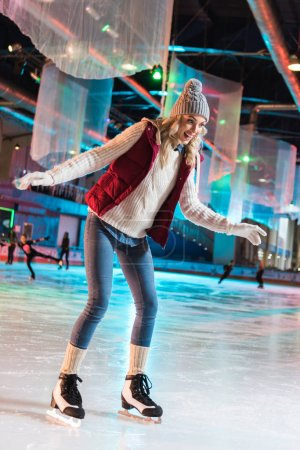 excited beautiful young woman ice skating on rink