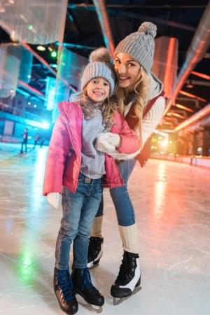 beautiful happy mother and daughter smiling at camera while standing together on skating rink