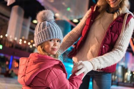 Photo pour Plan recadré de mère souriante et adorable petite fille tenant la main sur la patinoire - image libre de droit