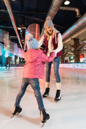 happy mother and daughter holding hands and looking at each other on skating rink