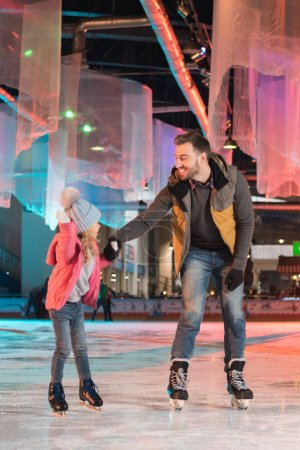 happy father and daughter ice skating together on rink