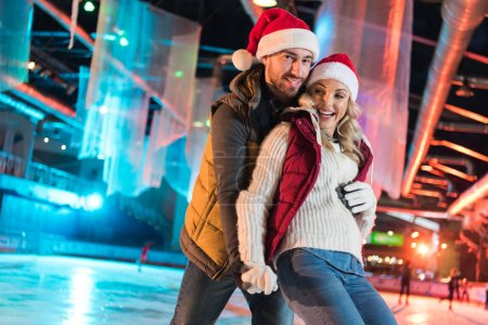 beautiful happy young couple in santa hats hugging and having fun on rink