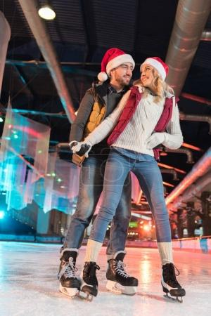 beautiful happy young couple in santa hats skating on rink