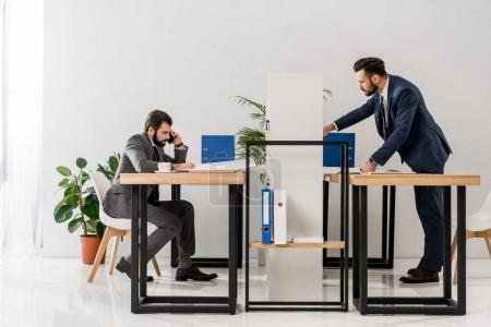 side view of businessmen working at tables in office