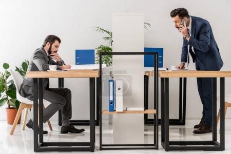 Photo pour Homme d'affaires, parler de smartphone à table dans le Bureau - image libre de droit