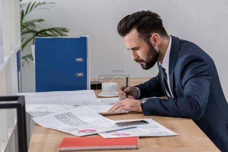 businessman sitting at table, looking at documents and writing something