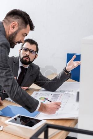 Photo pour Deux hommes d'affaires, faisant valoir à propos des documents au bureau - image libre de droit