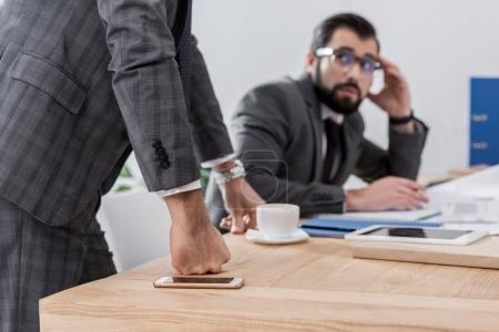 scared businessman sitting at table and looking at team leader