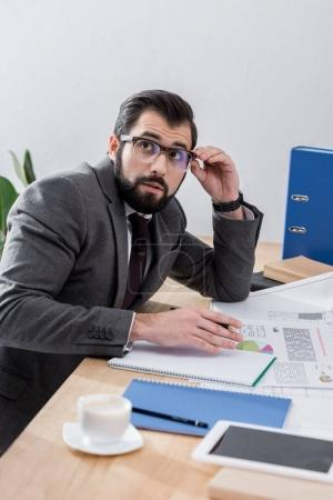 businessman sitting at table and looking up